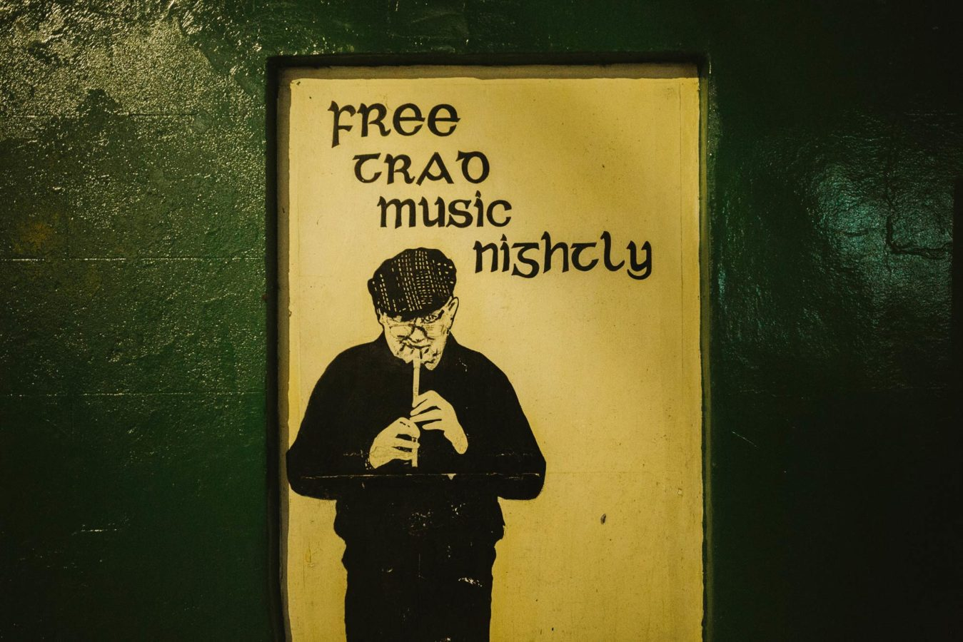 A picture of a man playing irish music on a pub wall