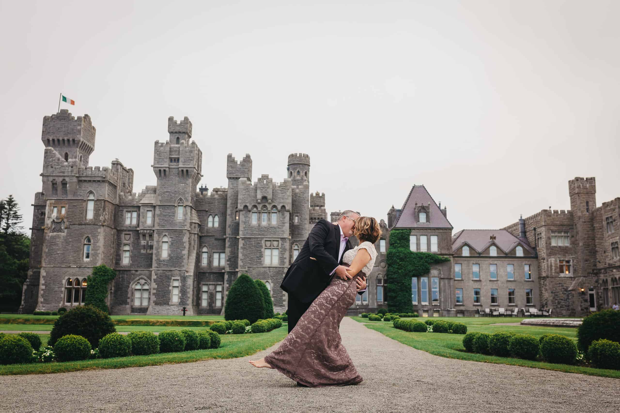 a couple kiss infront of ashford castle on their  Irish castle elopement