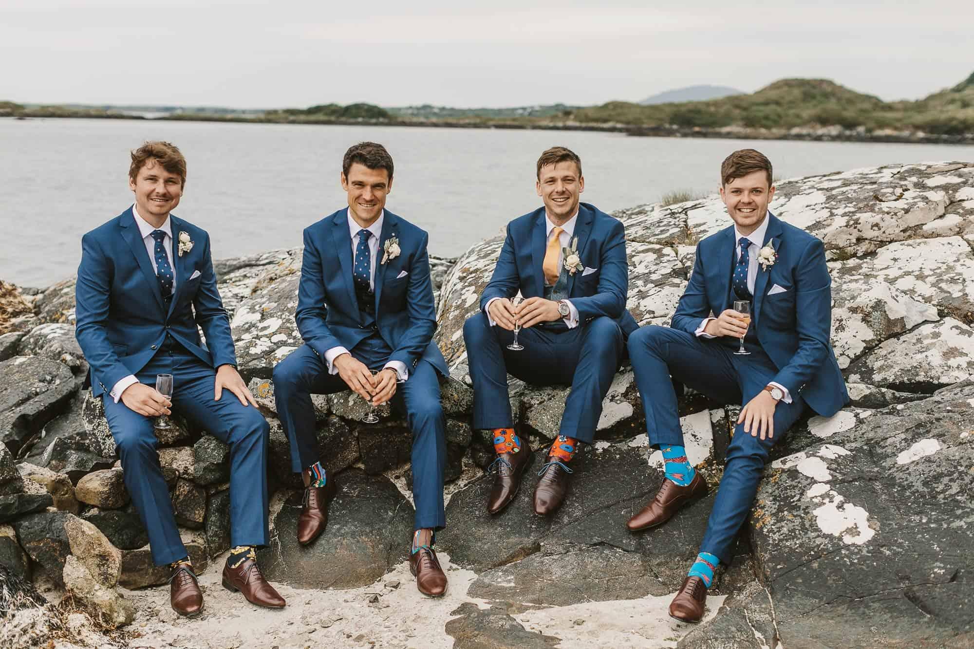 Elopement Ireland Connemara Groomsmen Style as they sit on the rocks