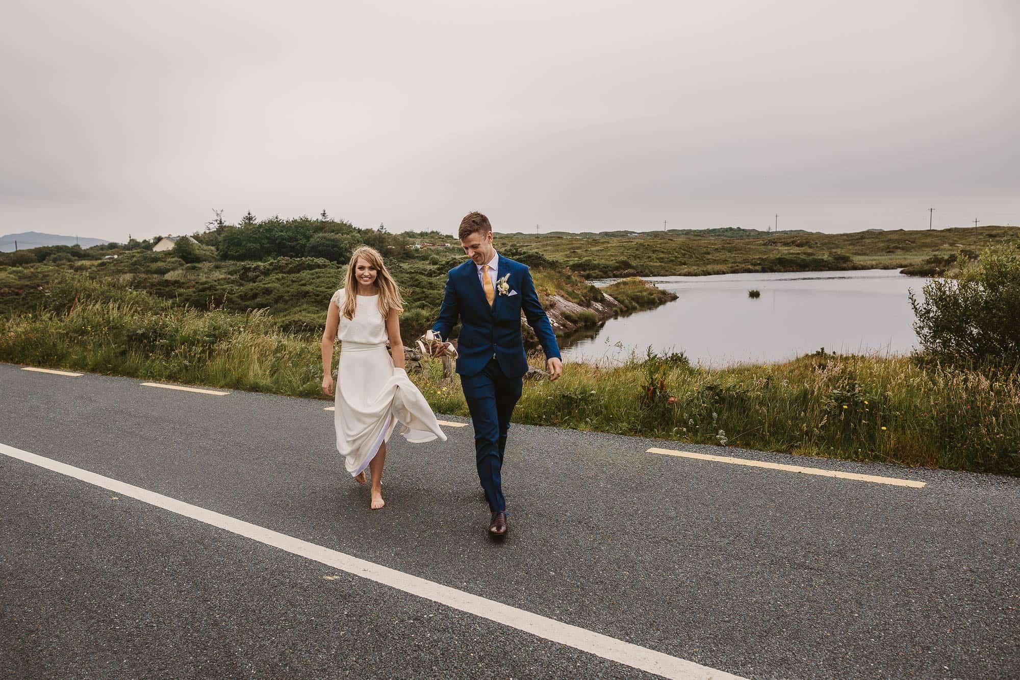 Elopement Ireland Connemara Barefoot Bride and groom are crossing the road