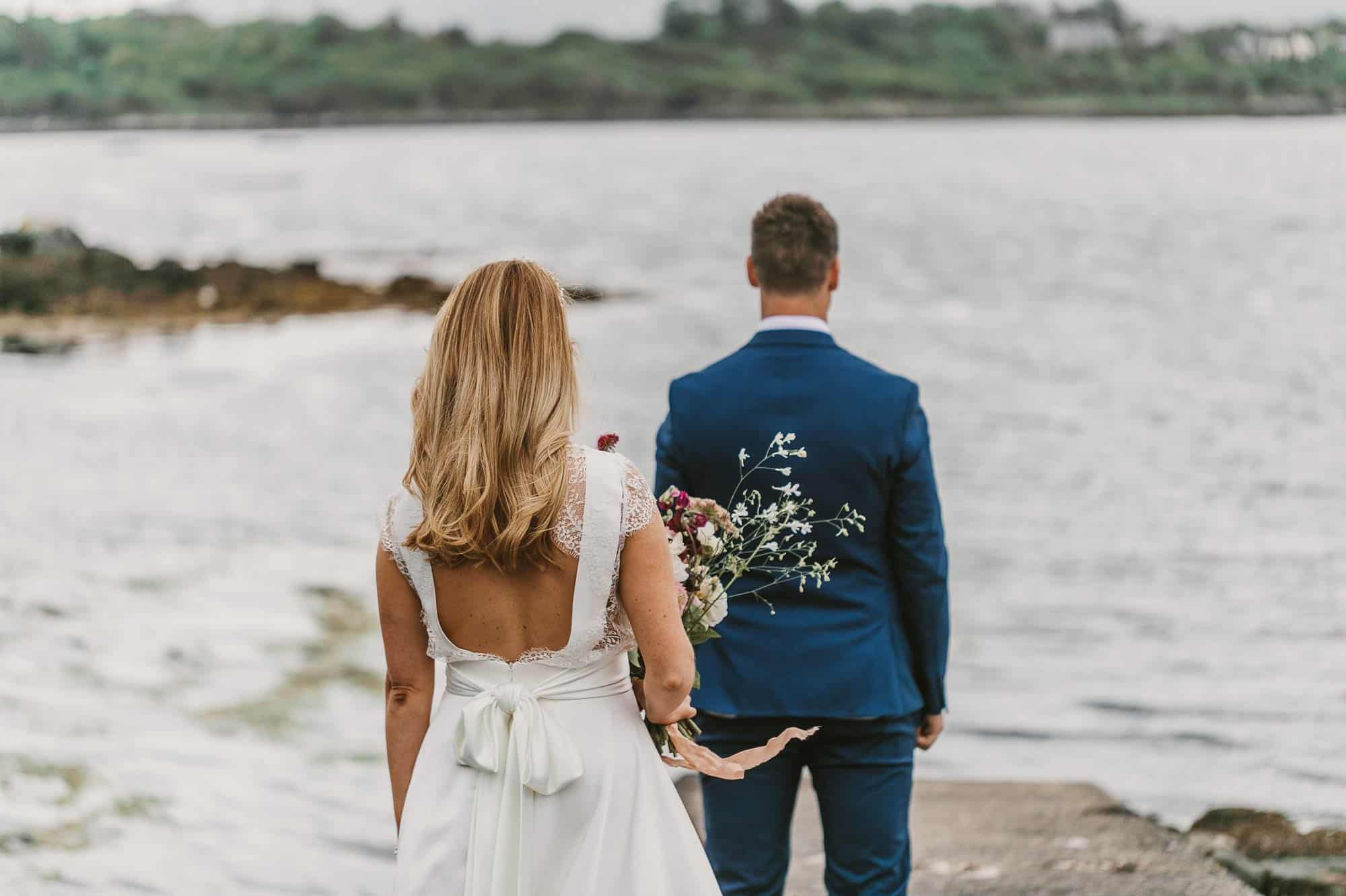 Elopement Ireland Connemara First Look on the Pier, Bride walking up to groom, at waters edge