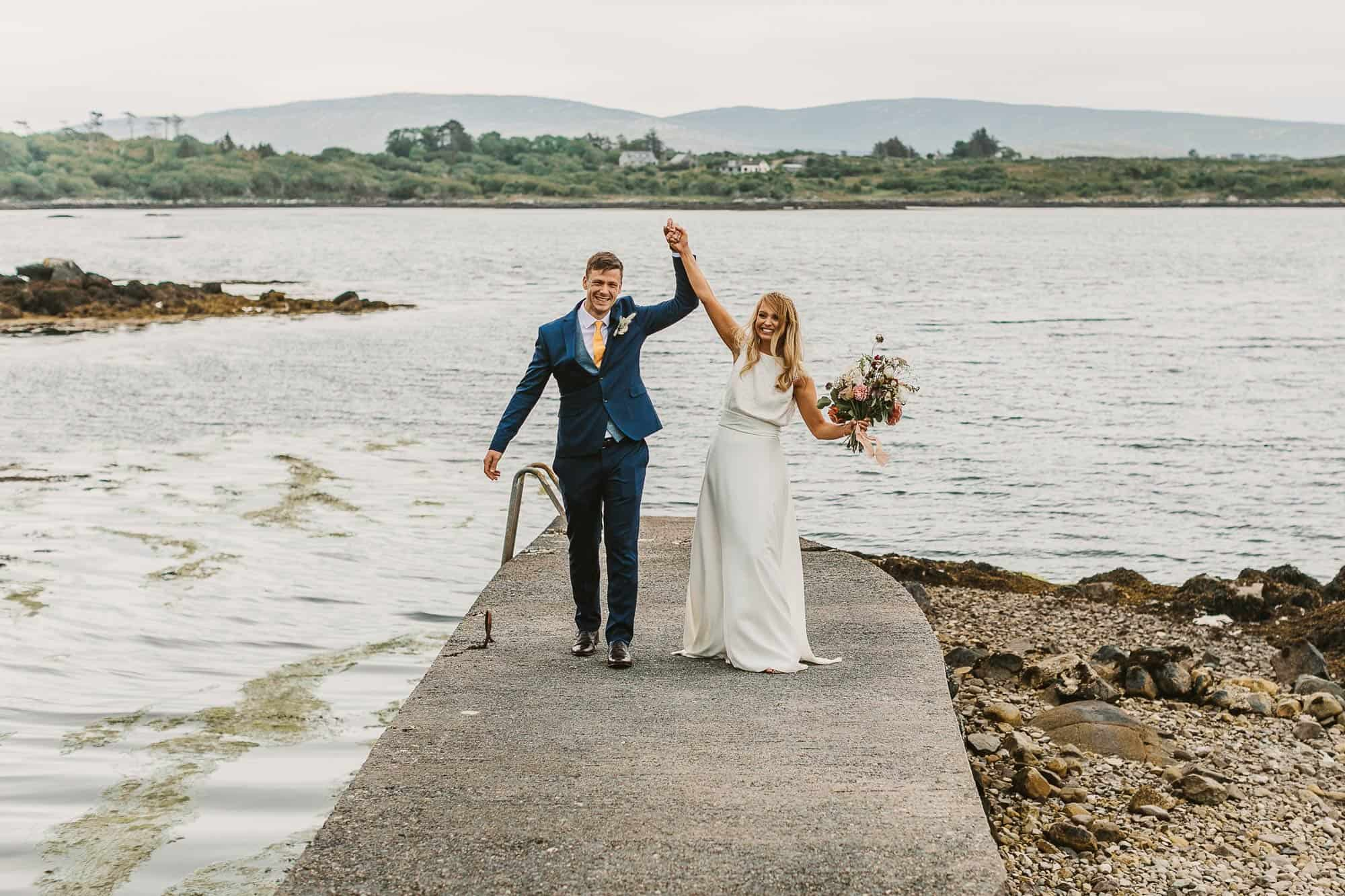Elopement Ireland Connemara Ireland Fun, couple are cheering with arms up on the pier