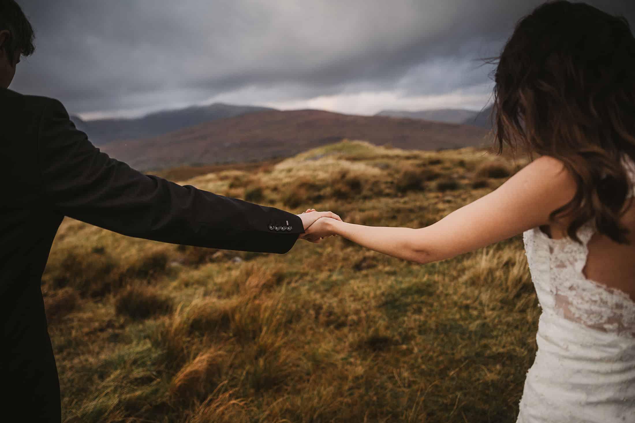 A couple holding hands as the hike through Connemara on their destination wedding Ireland