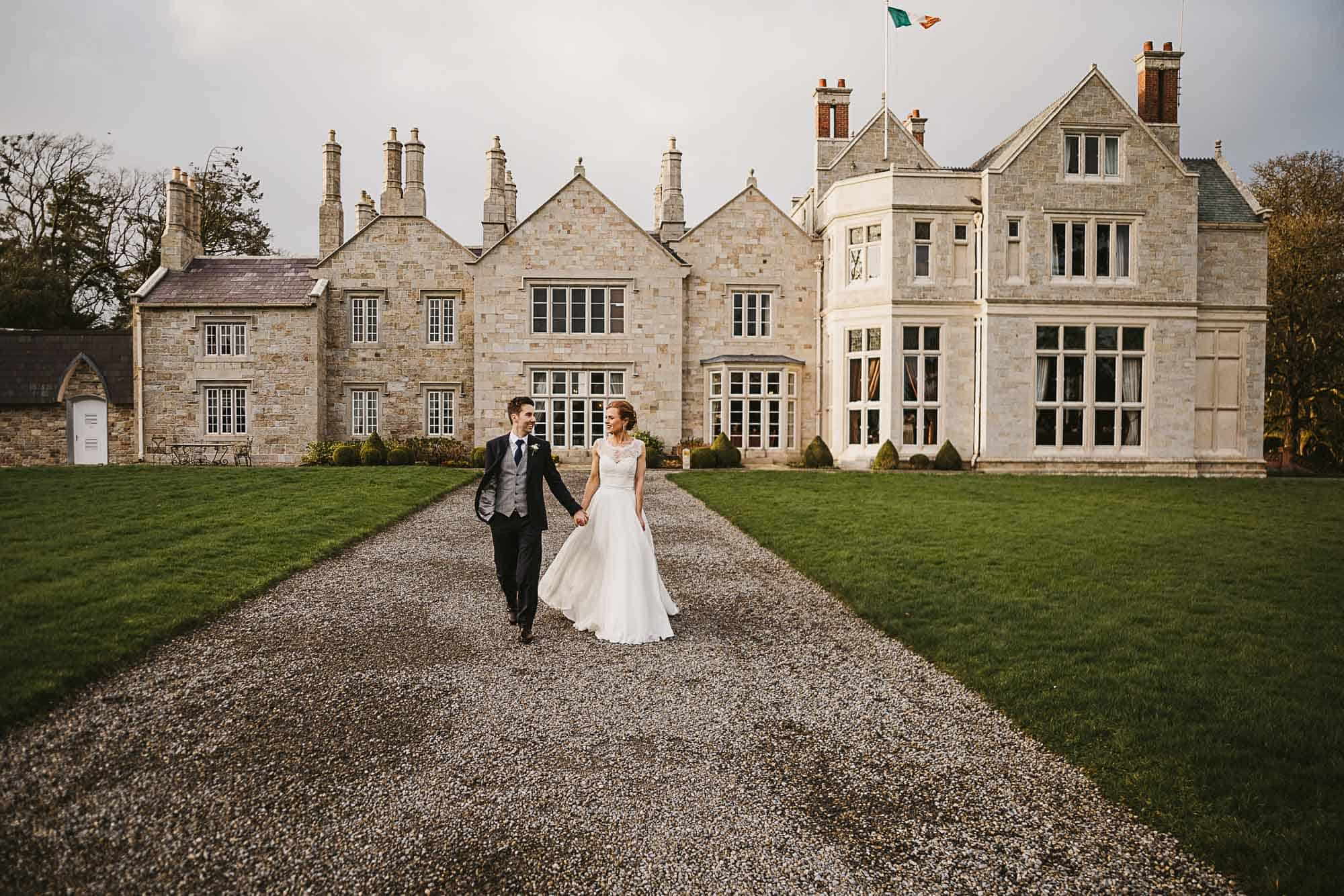 a couple walk in front of their castle on their  Irish castle elopement