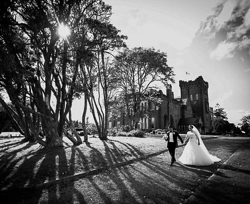 destination wedding Ireland at an Irish Castle. A couple stroll on the grounds in the winter sun as they elope to Ireland