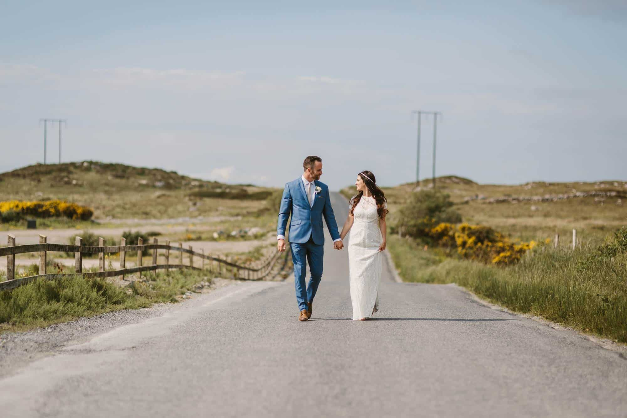 Elopement videographer Ireland, couple walk on a road
