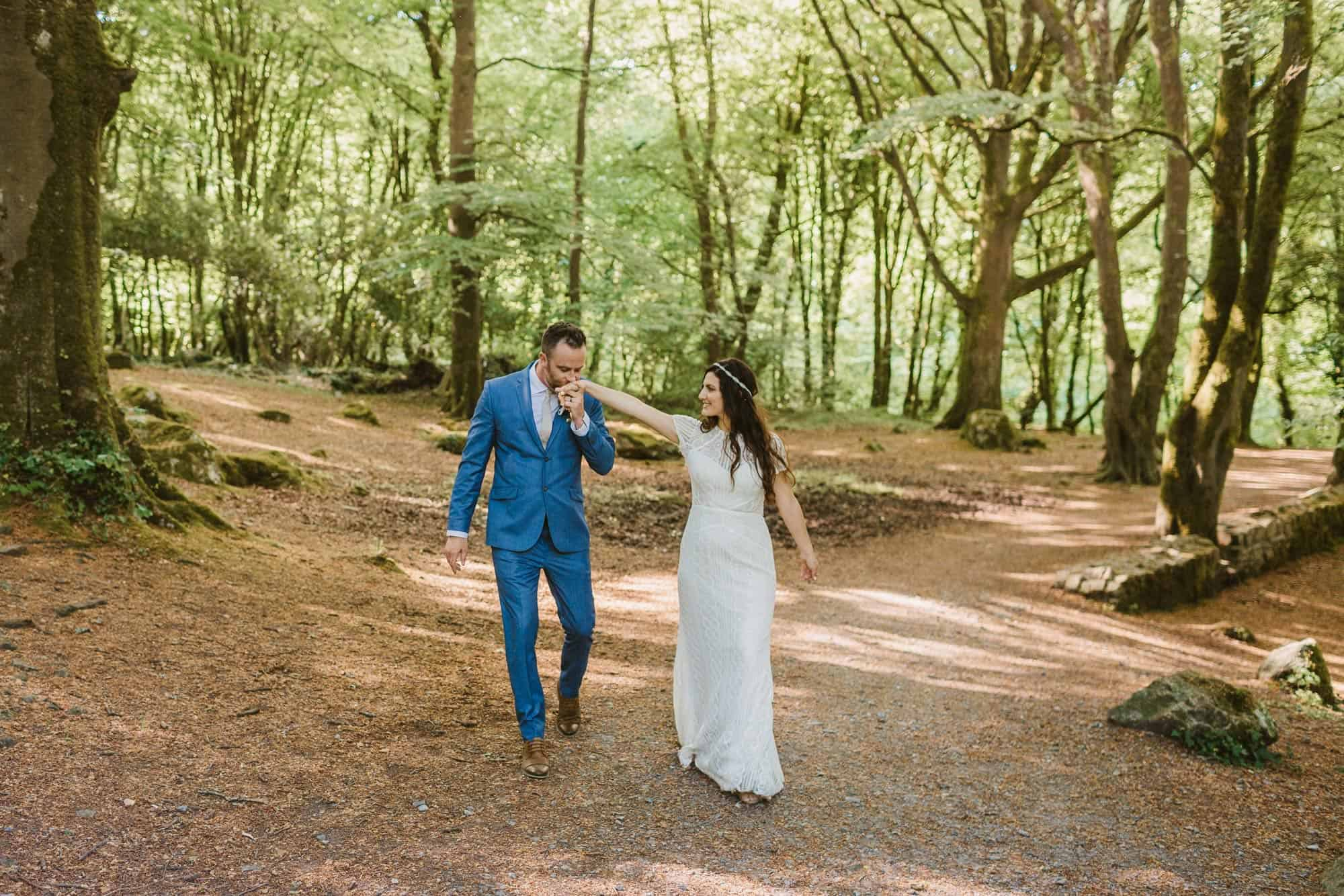 Elopement videographer Ireland, groom kissing brides hand in forest
