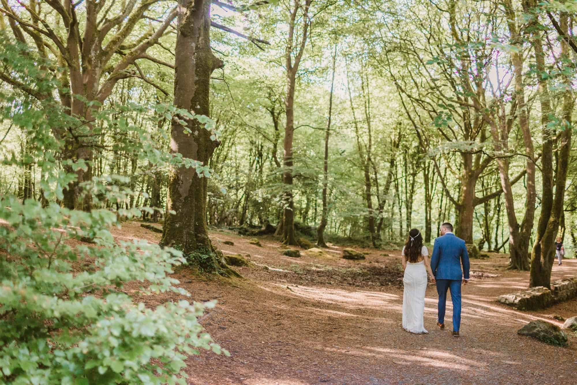 Elopement videographer Ireland, couple walking away in forest