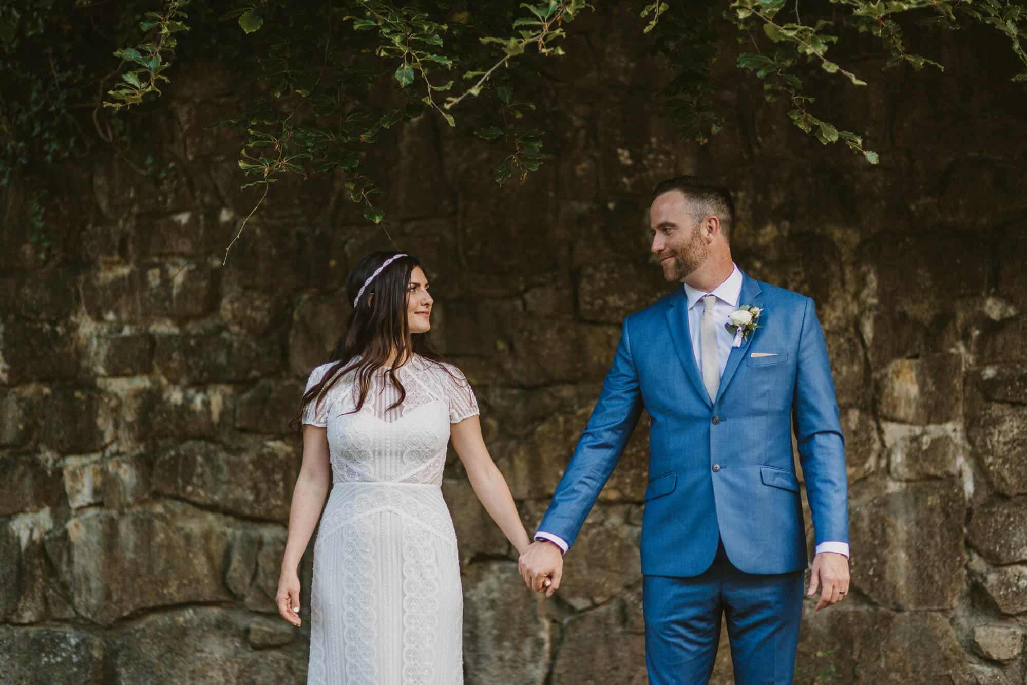Elopement videographer Ireland, couple hold hands in front of stone wall