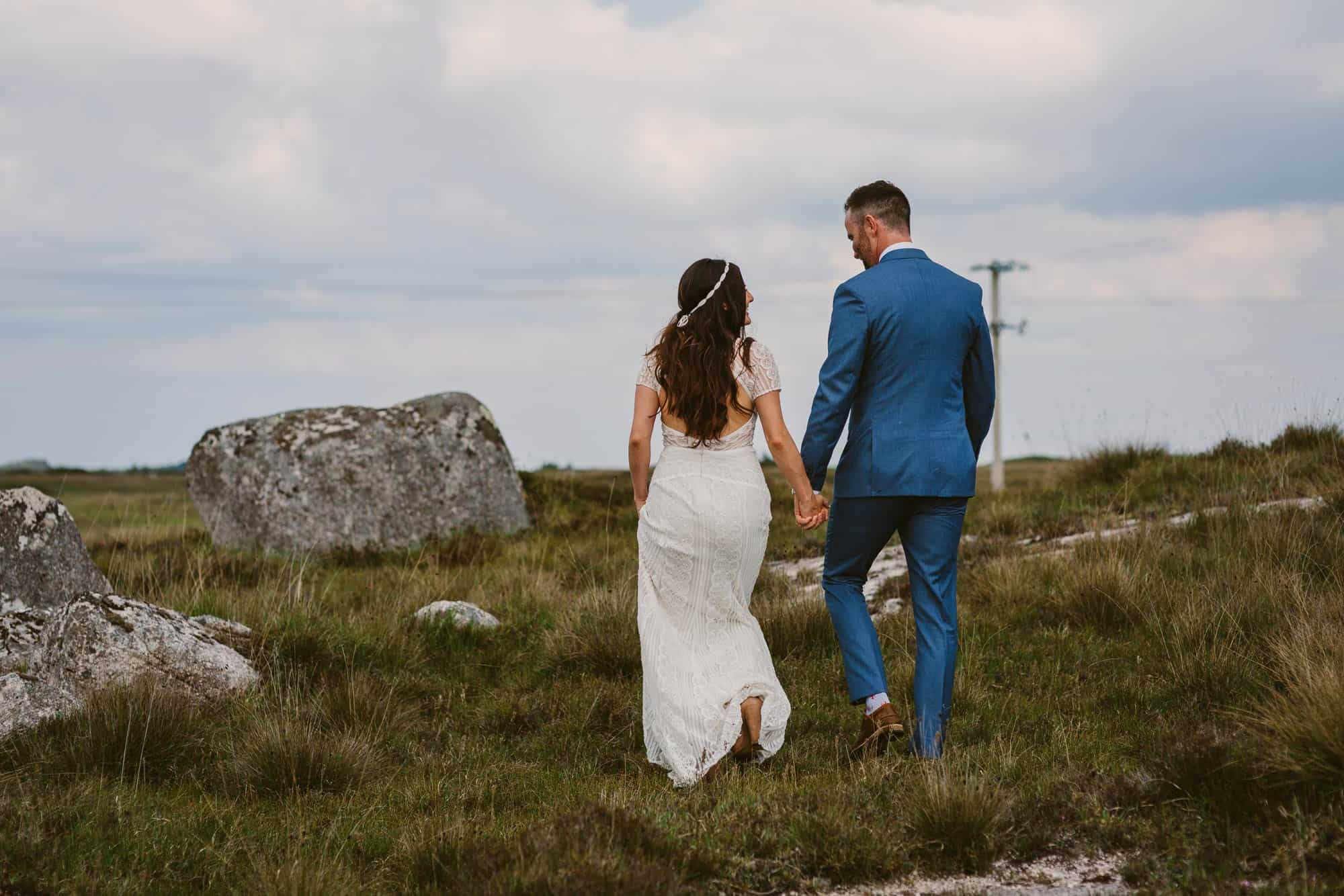 Elopement videographer Ireland, couple walk through a field