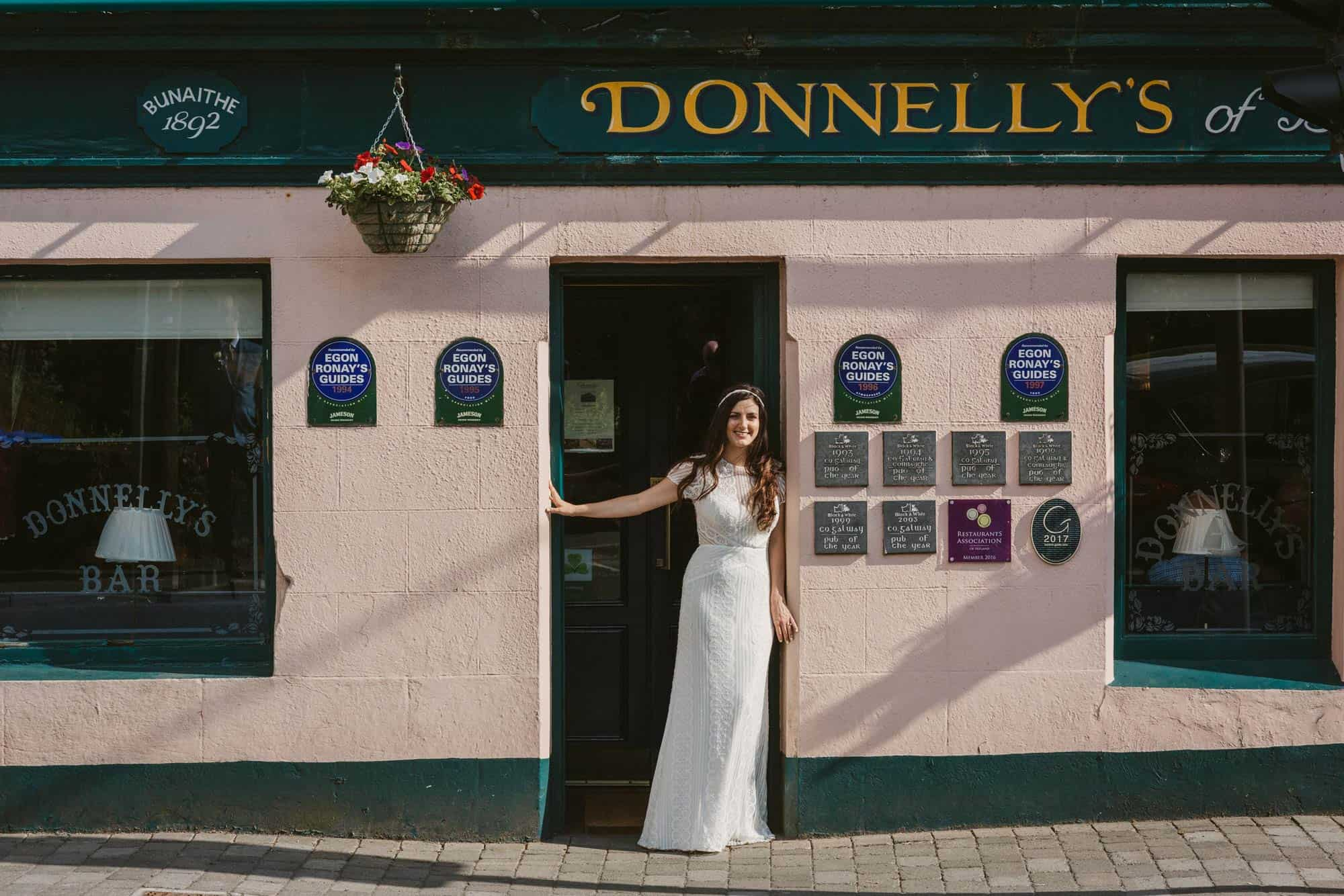 Elopement videographer Ireland, bride in Irish pub doorway