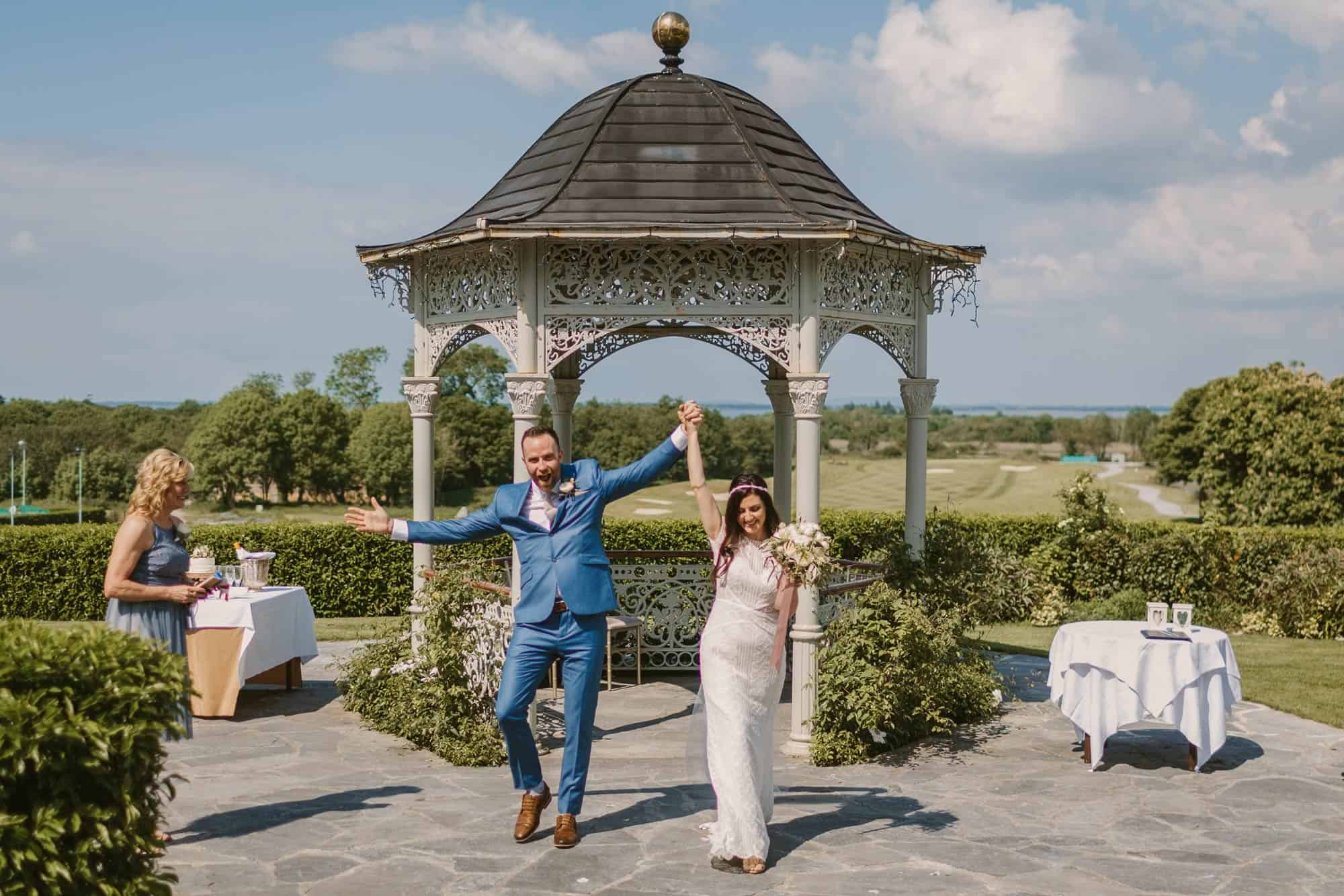 Elopement videographer Ireland, couple cheer with arms in the air