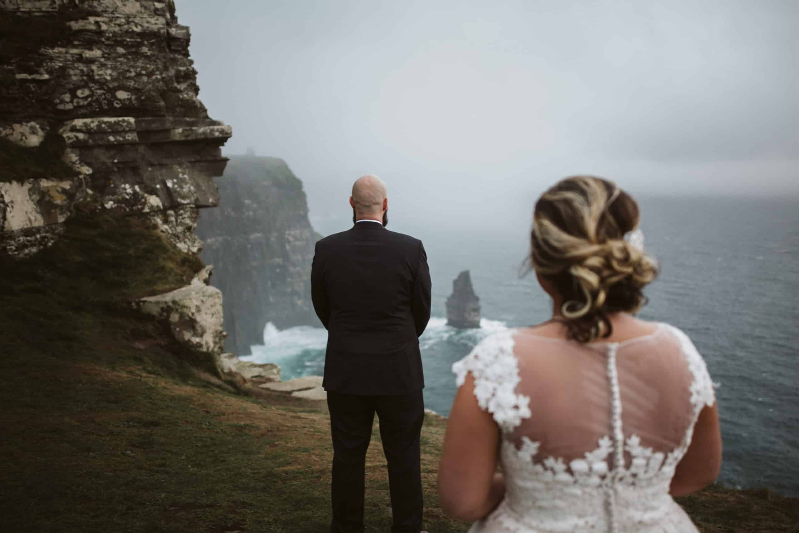 Ireland Cliffs of Moher Wedding Hags head First Look, bride is walking up behind the groom