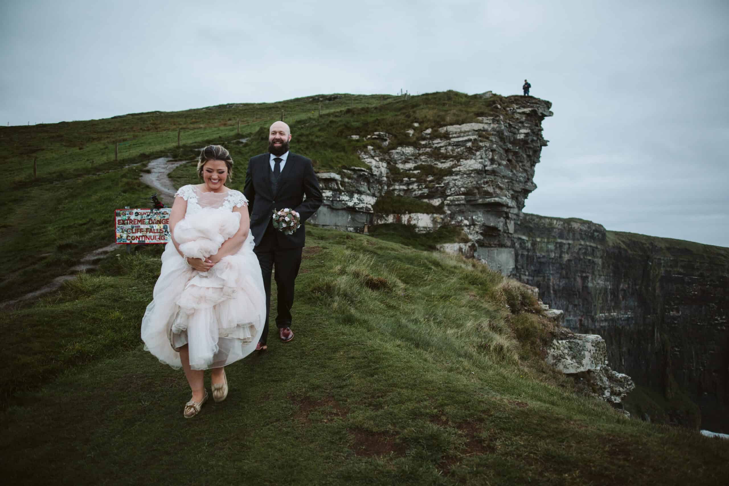 Cliffs of Moher Wedding Hags head, bride is holding her dress up as she walks