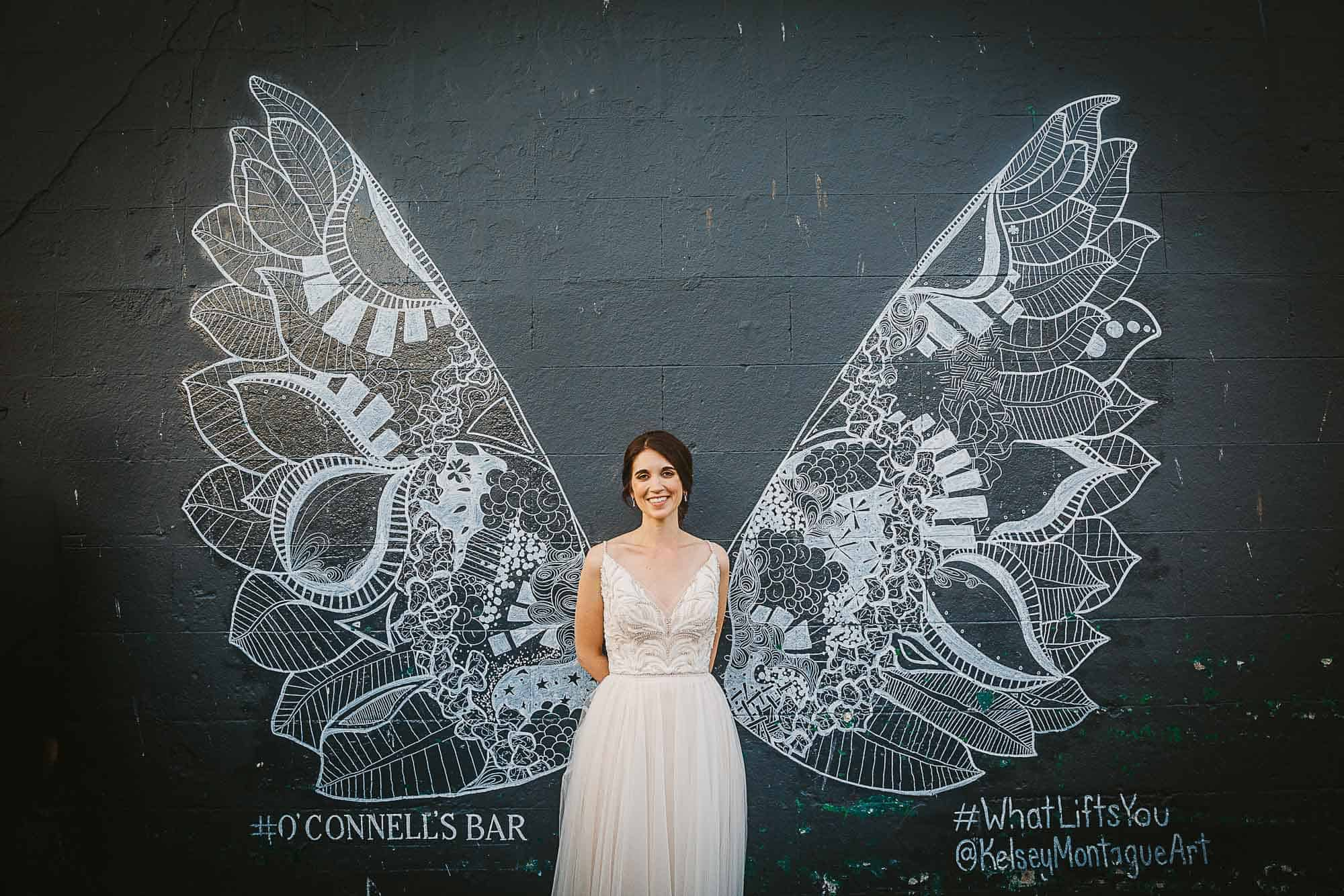 Galway City Elopement Fun, A beautiful angel, a bride stand against angel wings - street art on her Destination Wedding in Ireland