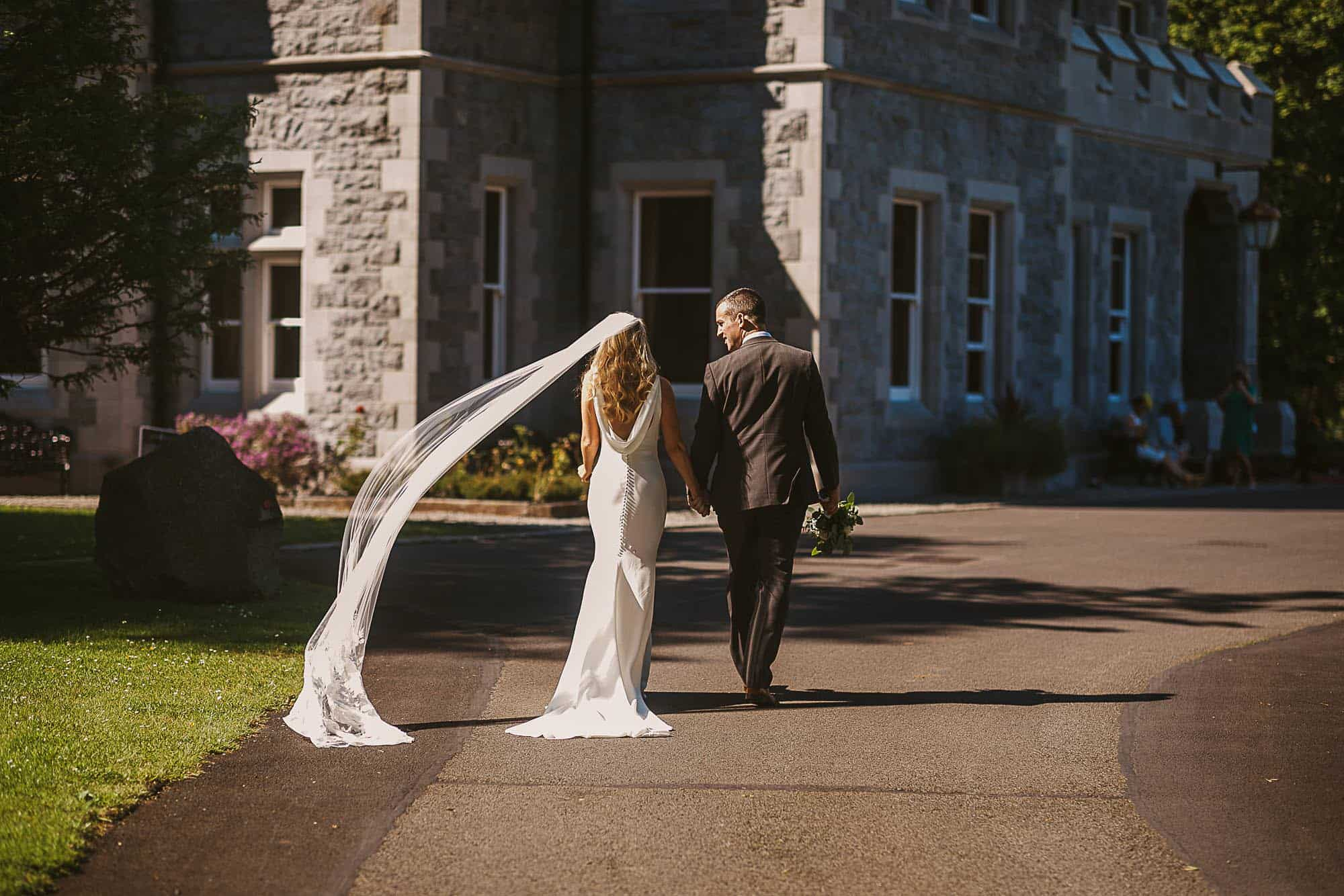 a coulple holding hands and walk towards their castle on an Irish castle elopement