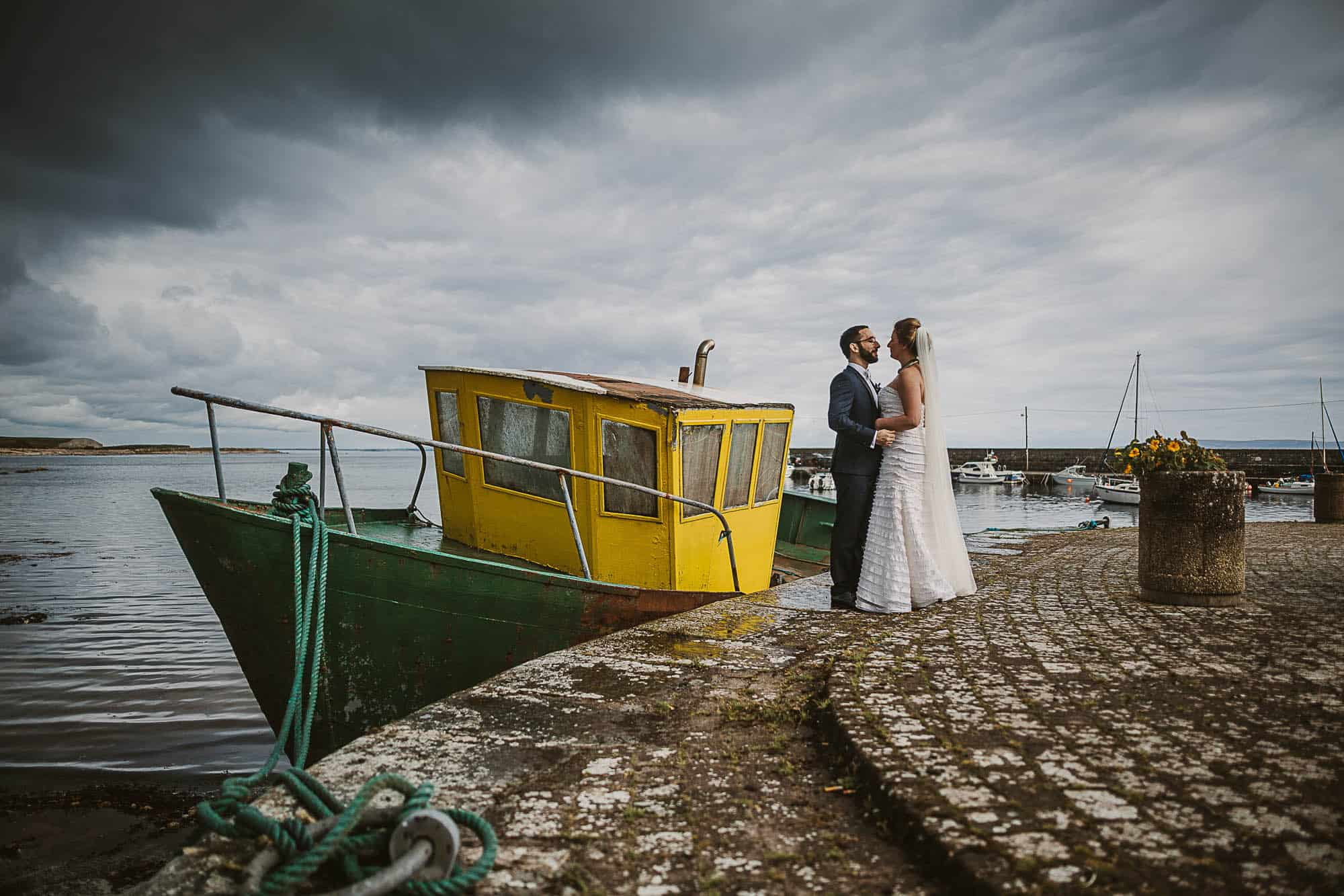 Galway City Elopement Fun down on the pier a couple hold hands on their Destination Wedding in Ireland
