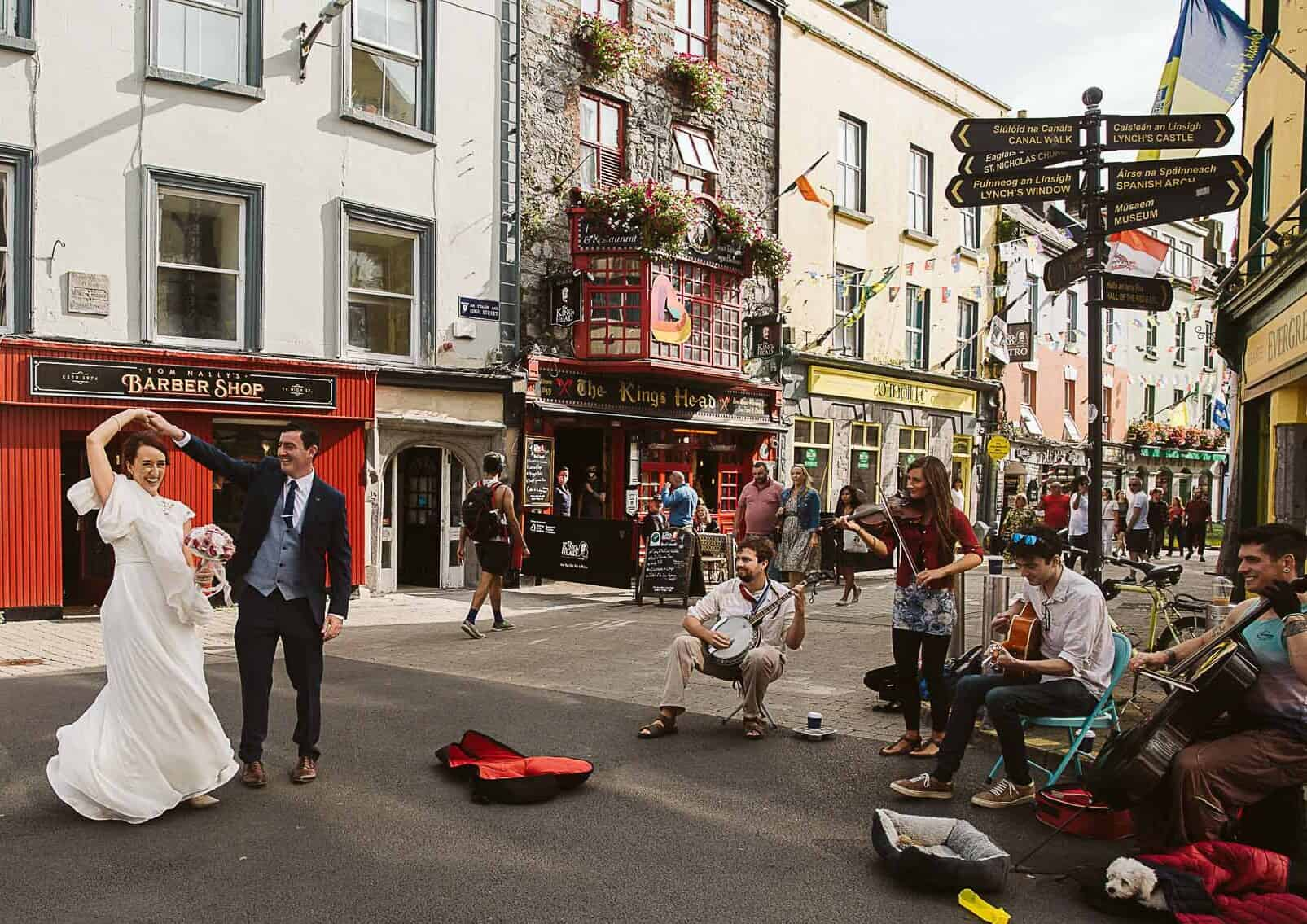Galway City Elopement Fun, a couple dancing on the streets to buskers music on their Destination Wedding in Ireland