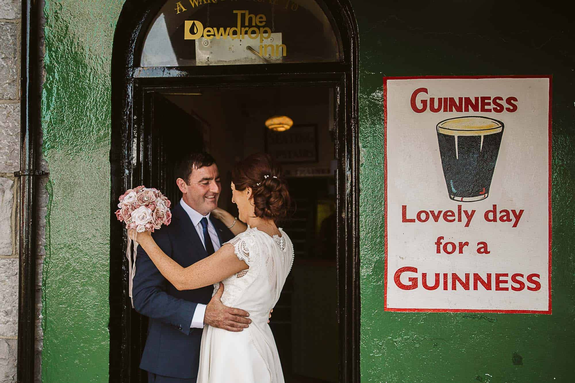 Galway City Elopement Fun, A couple hug in the doorway of a pub, organized but their wedding planner Ireland