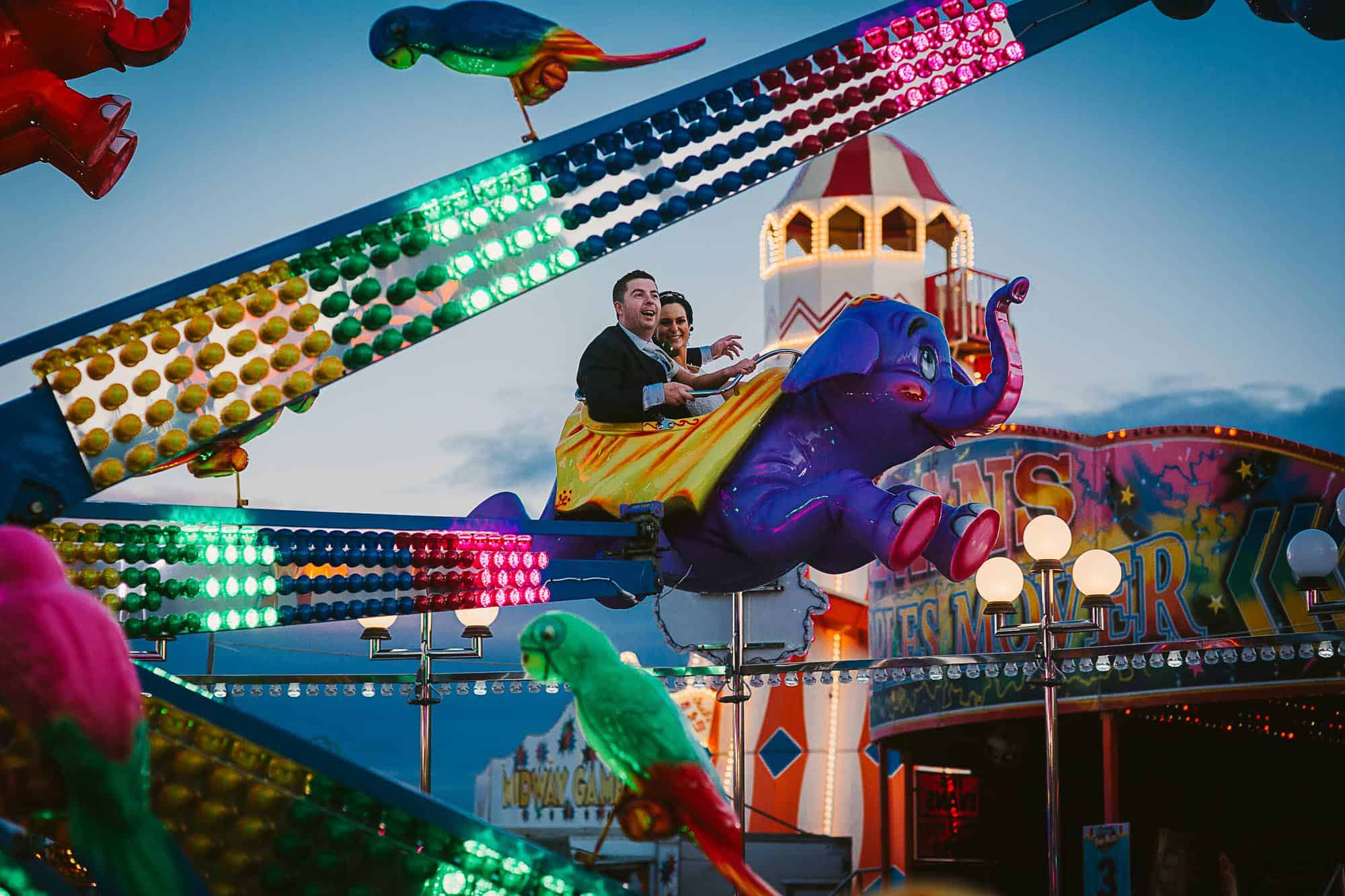 Fun on your Galway City Elopement, couple in leisureland on the elephants , laughing up in the sky after their celtic wedding ceremony
