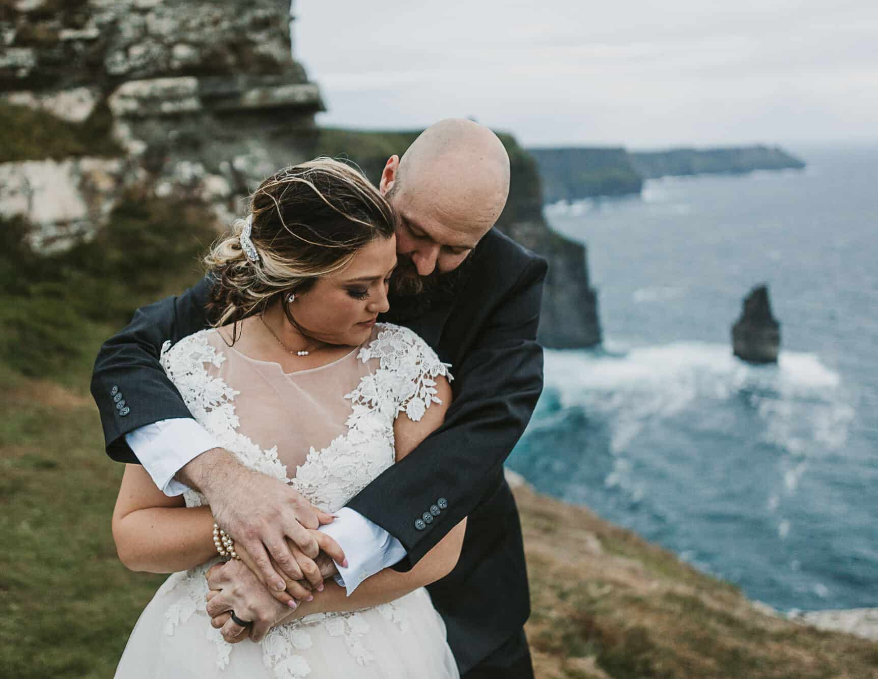 Cliffs of Moher elopement in Ireland, a couple hold each other on the cliffs after deciding yes we should elope