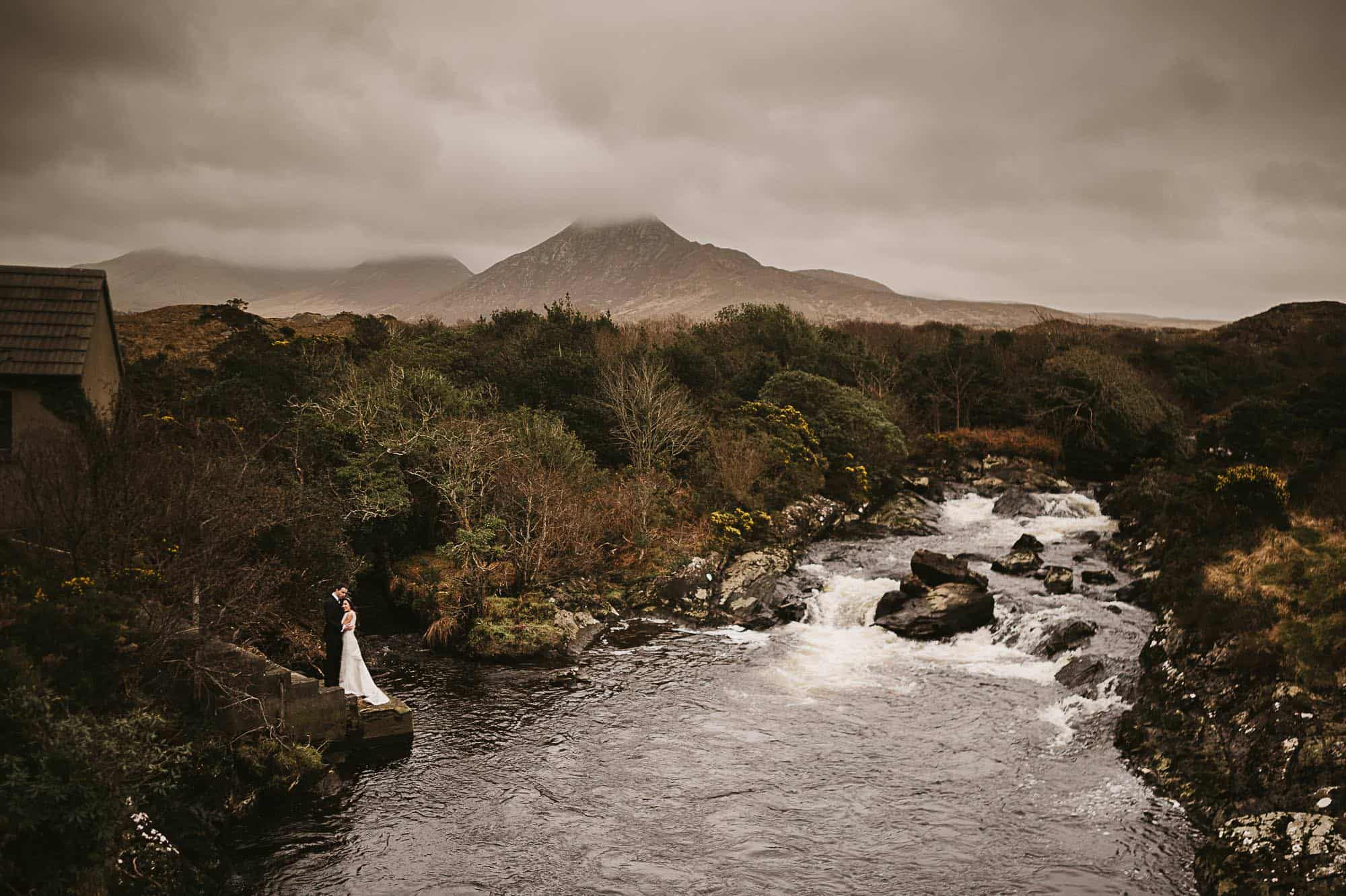 Connemara elopement, A couple hold each other by the edge of a river organized but their wedding planner Ireland