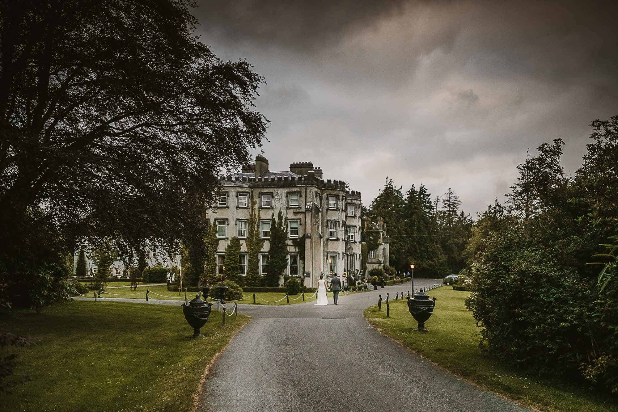 a couple stroll on the grounds on their Irish castle elopement