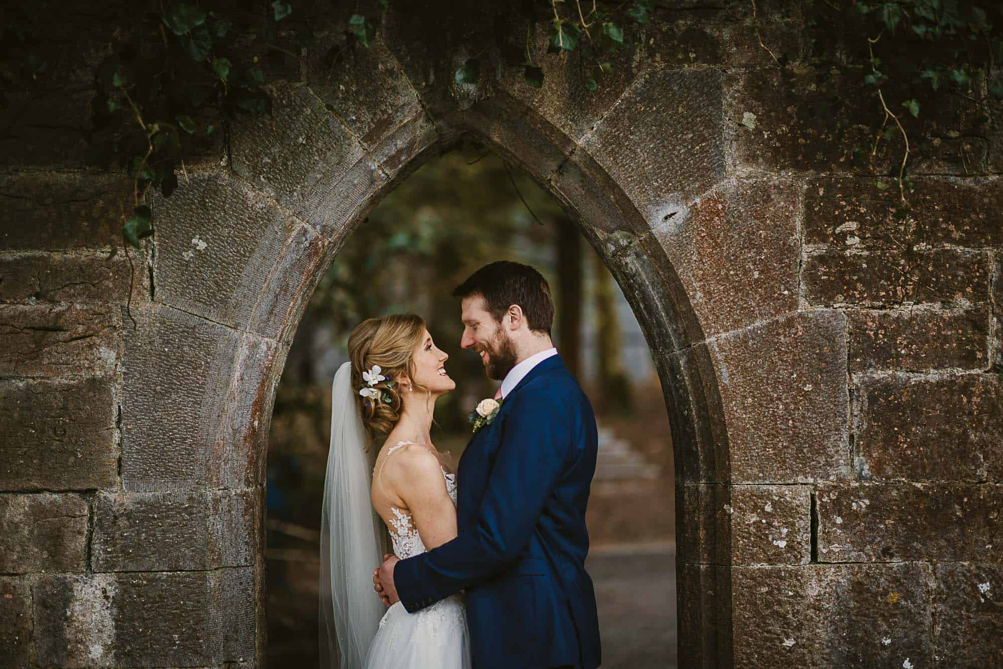 a couple hugging in and archway of a ruin on their  irish castle elopement