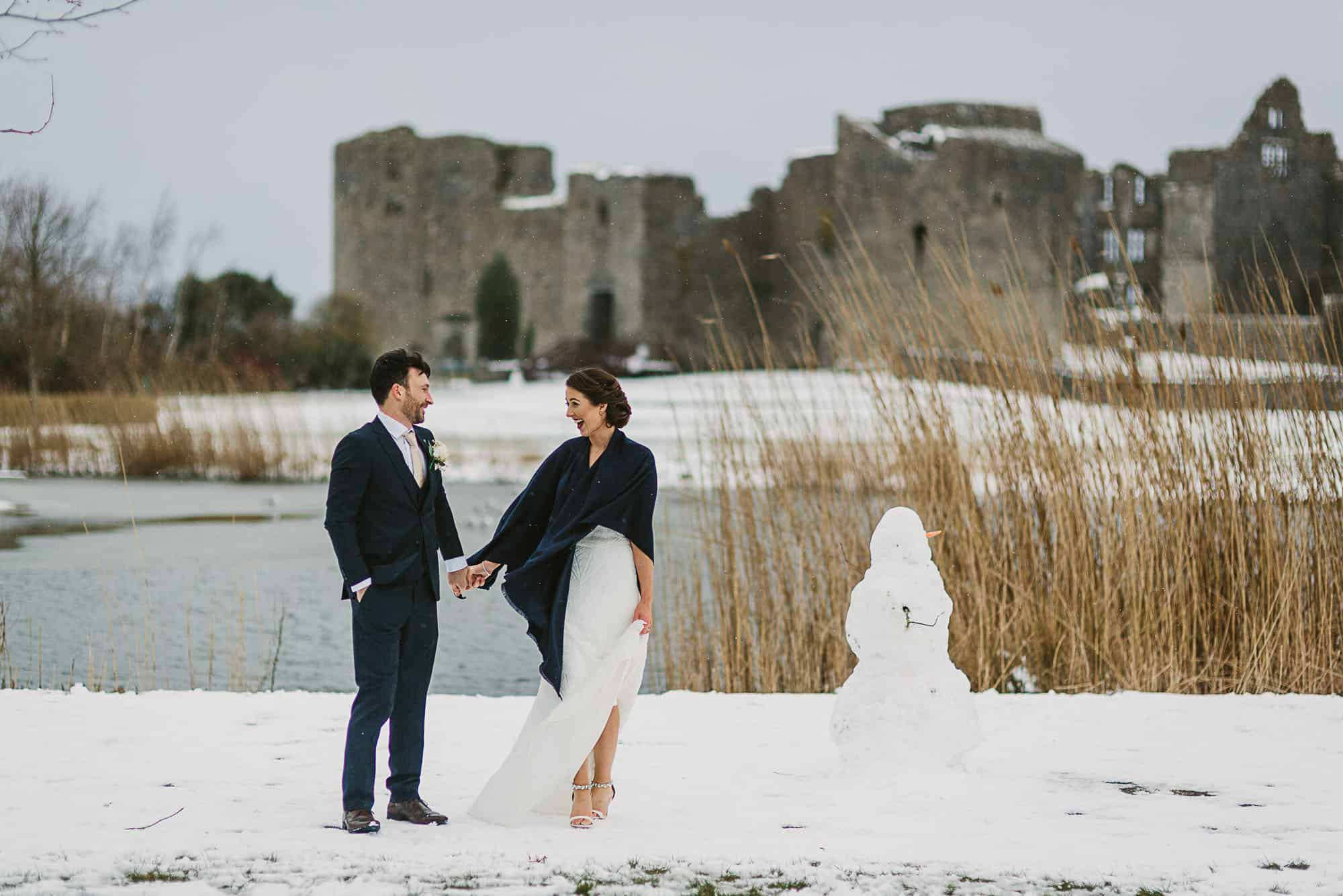A couple hold hand in the snow smiling on their irish castle elopement