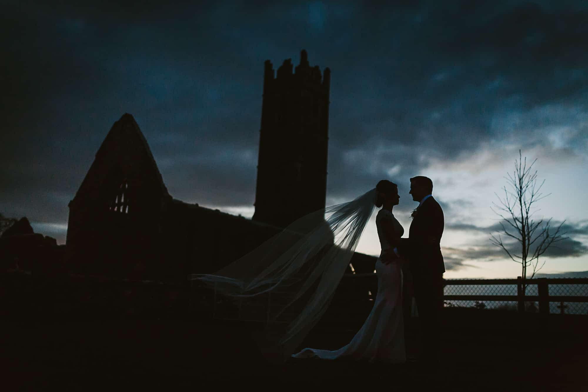 A couple are silhouetted at the ruins of corcomroe abbey on their  irish castle elopement