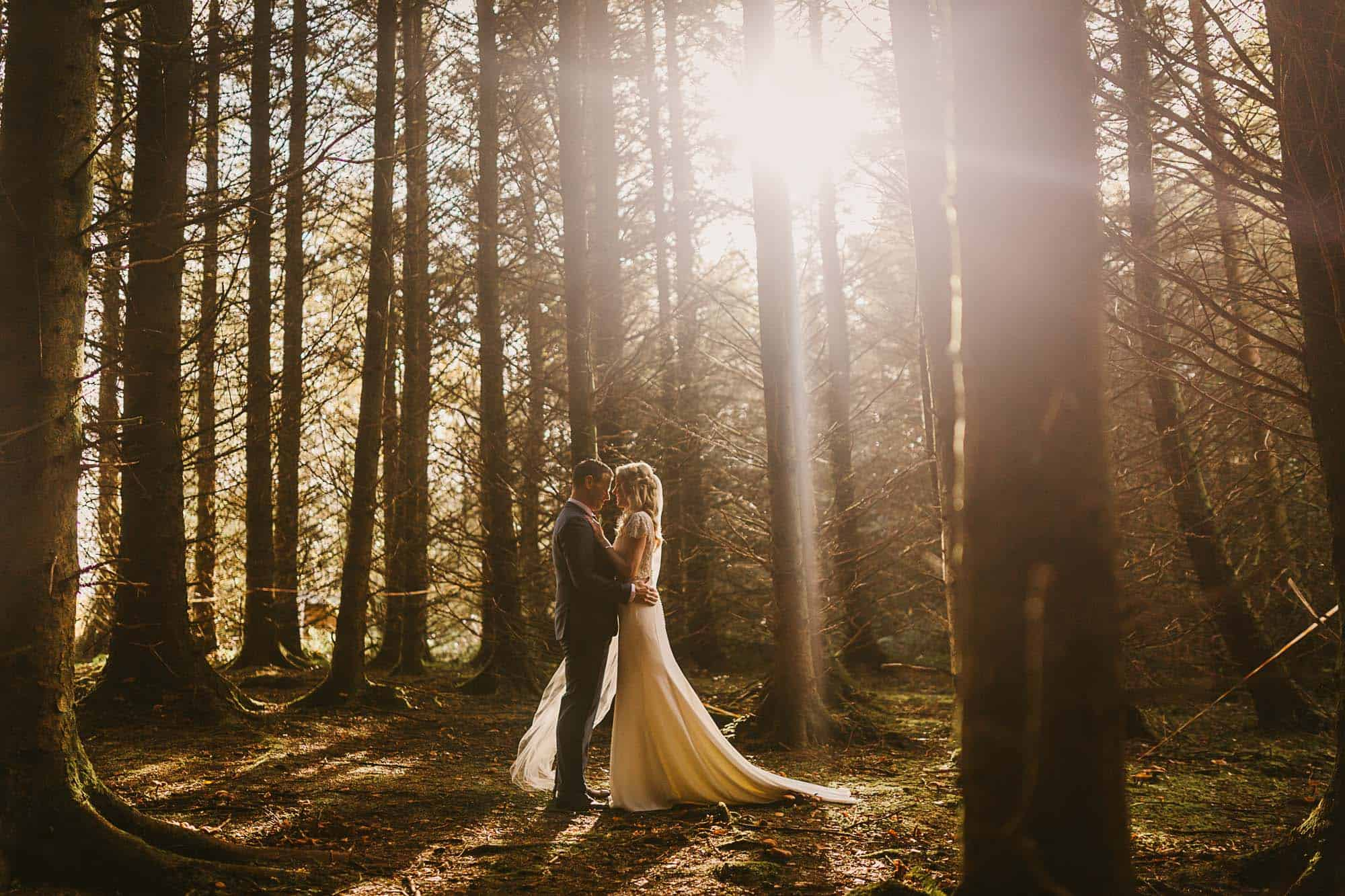 elope to ireland for the winter sun shining through the trees in a forest as a couple stand close on their destination wedding Ireland