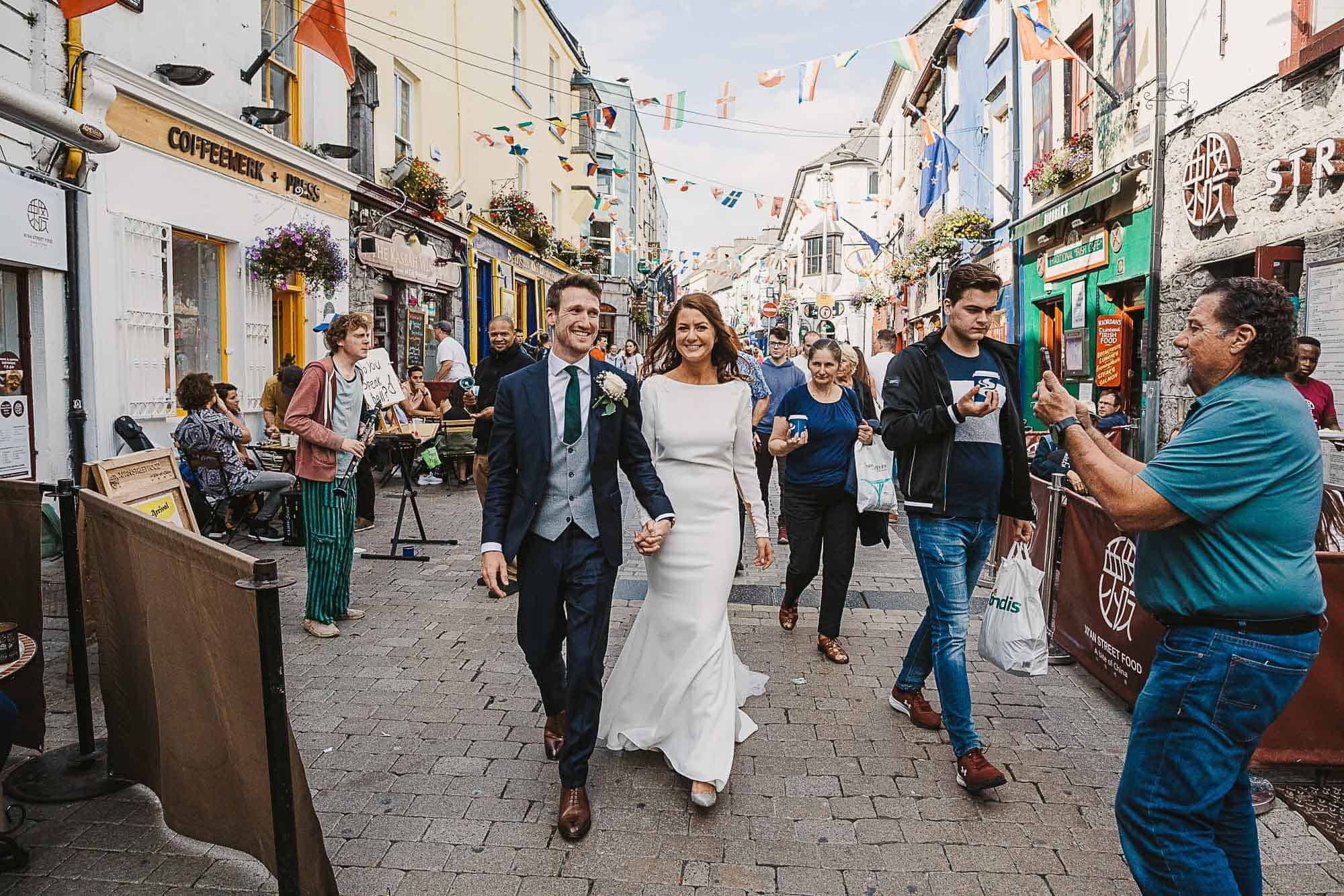 best places to elope, elopement planner Galway, Bride is wearing a long sleeve wedding dress as couple walk through busy street